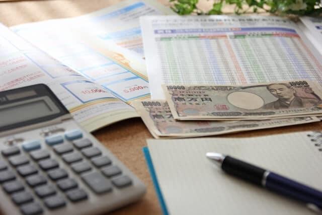 保険資料と電卓とお金